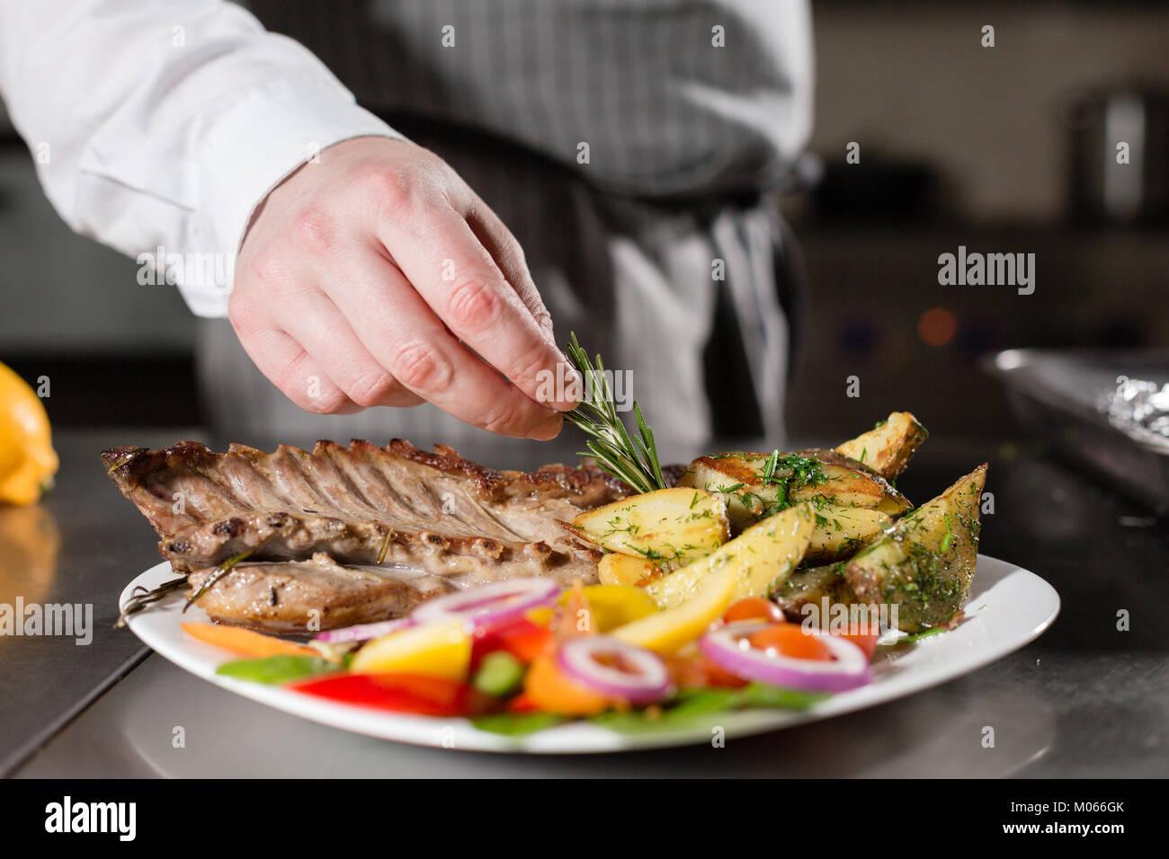 Der Küchenchef im Restaurant. Gegrillter Lammrücken mit Bratkartoffeln und frischem Gemüse. closeup Stockfoto