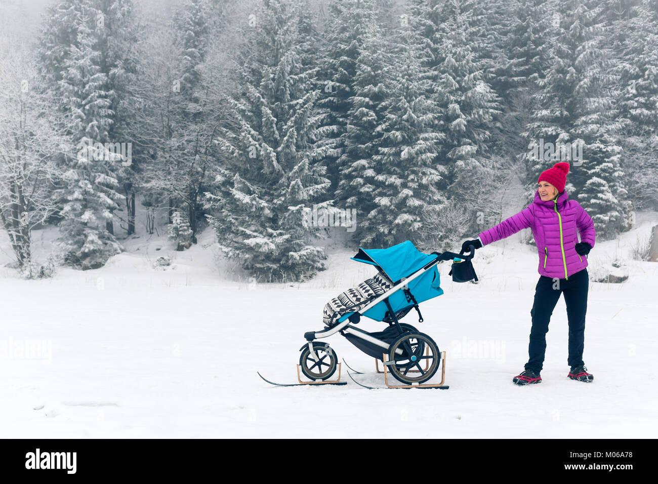 Mutter mit Baby Stroller genießen Mutterschaft im Winter Wald, in den Bergen. Joggen oder Walken Frau mit Schlitten Stockbild