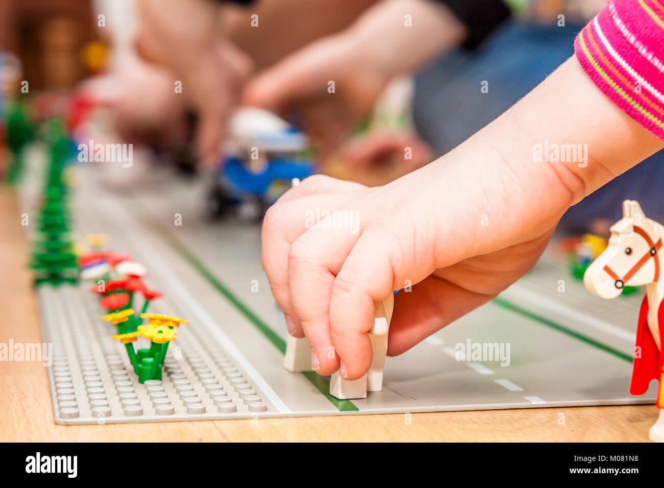 Preschooler Mädchen spielen mit bunten Spielzeug Blöcke und Steine Stockbild