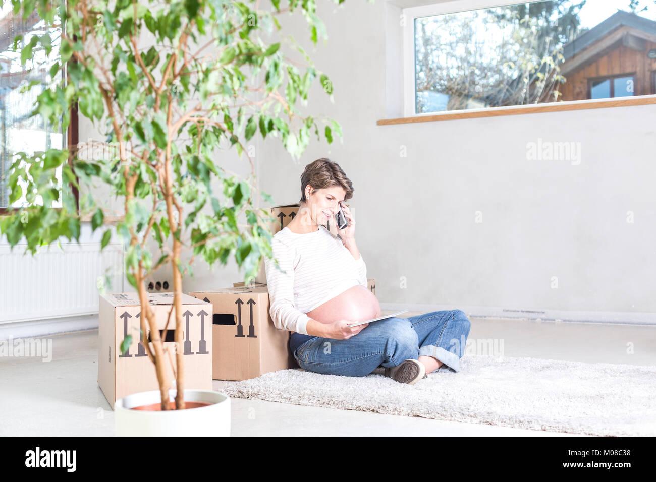 Schwanger Frau telefoniert beim Umzug sitzend im neuen Haus Stockbild