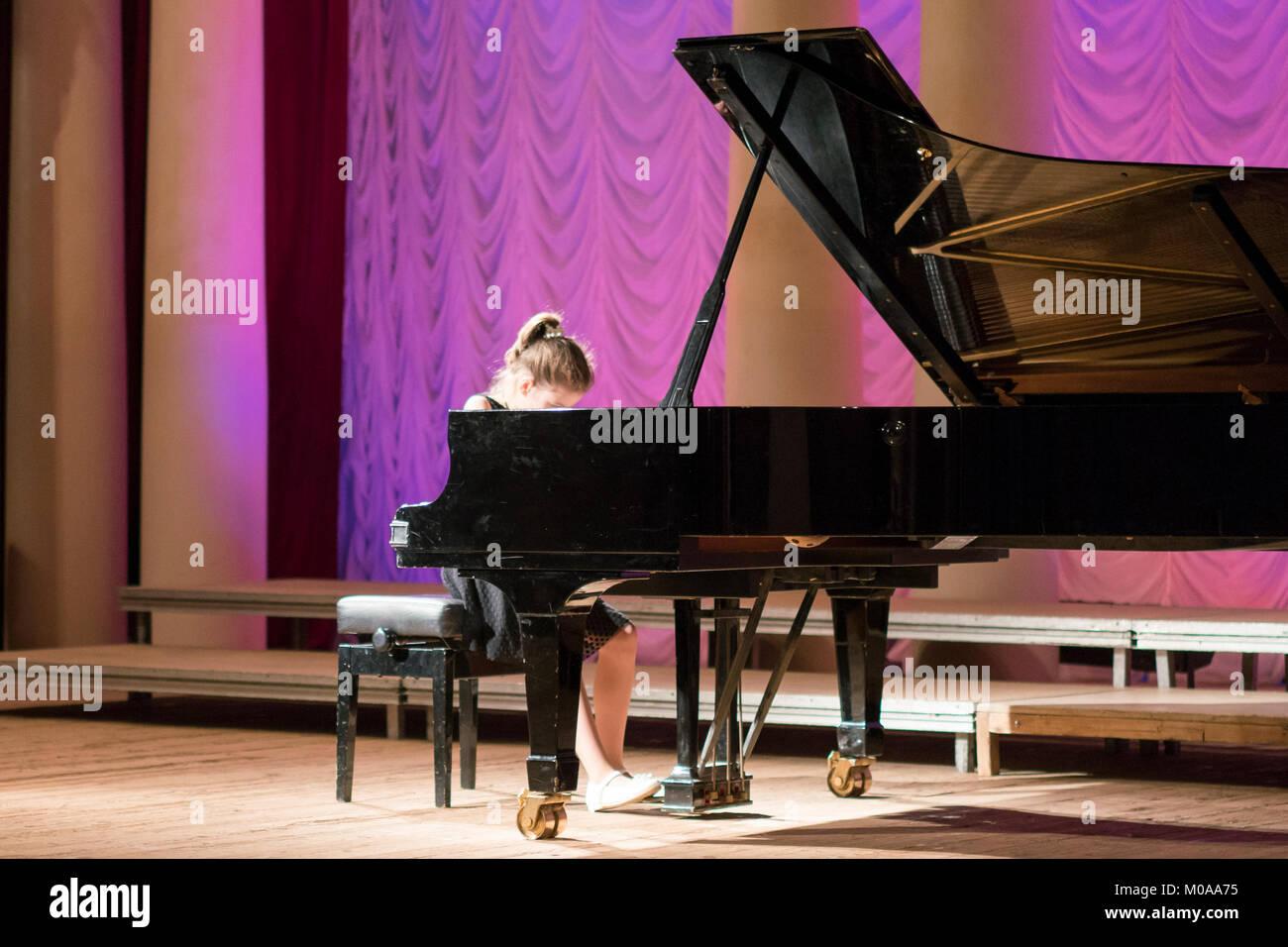 Kleines Mädchen spielt auf einer großen schwarzen Piano Stockfoto
