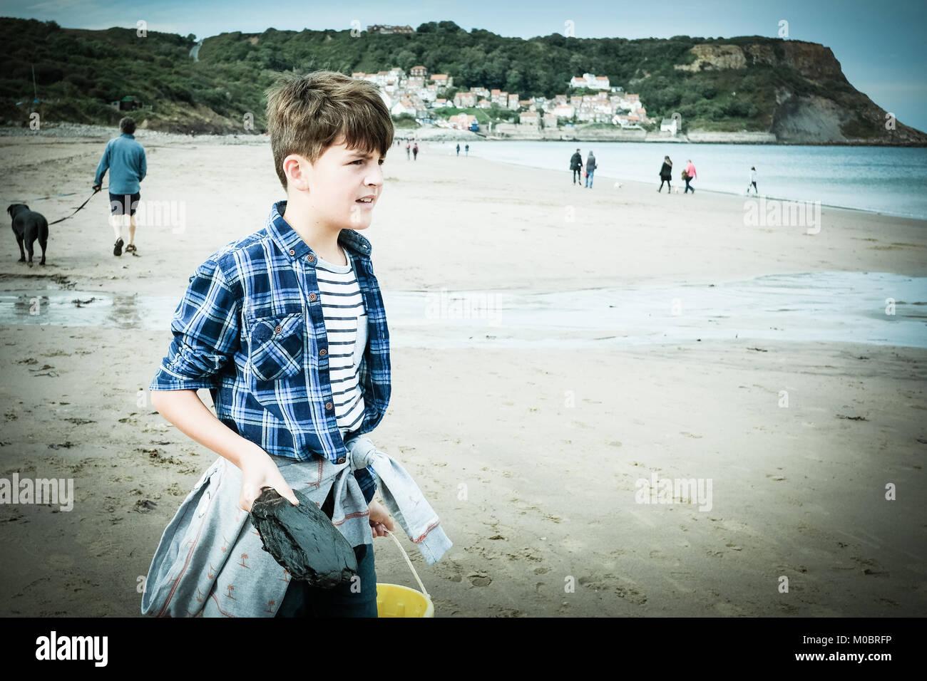10 Jahre alte dunkelhaarige Junge geniessen Urlaub am Strand, [Songbook] Bay, Yorkshire, Großbritannien. Stockbild