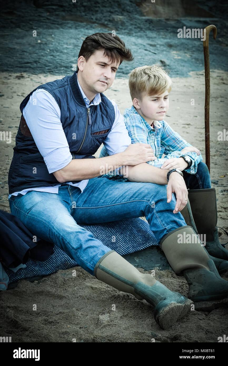 Vater und Sohn sitzen auf den Felsen am Strand und schaute nachdenklich, traurig, introspektive, [Songbook] Bay, Stockbild