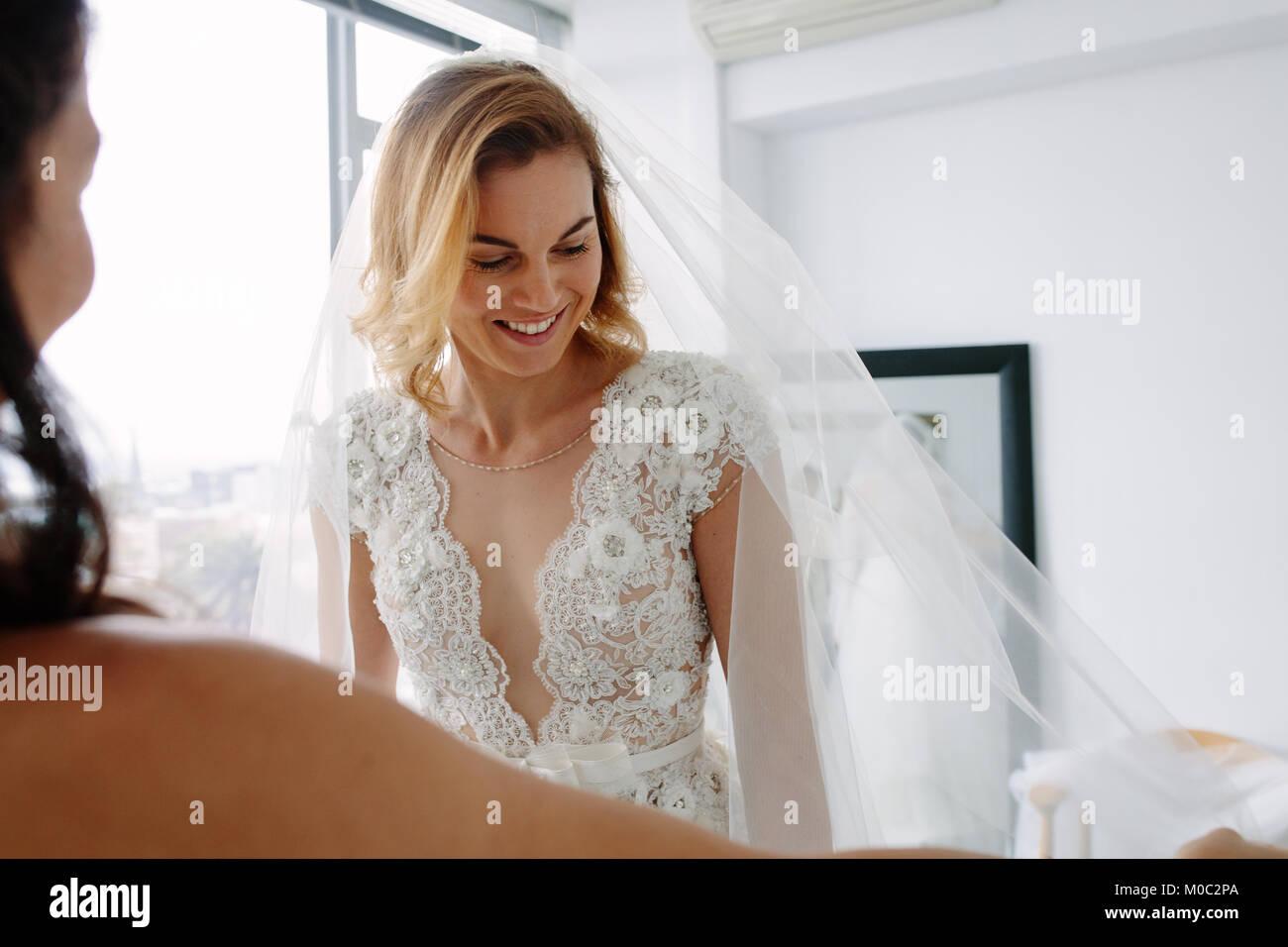 Schöne junge Frau, die versucht, auf Hochzeit Kleid in bridal Shop mit Assistant. Zukünftige Braut die Stockbild