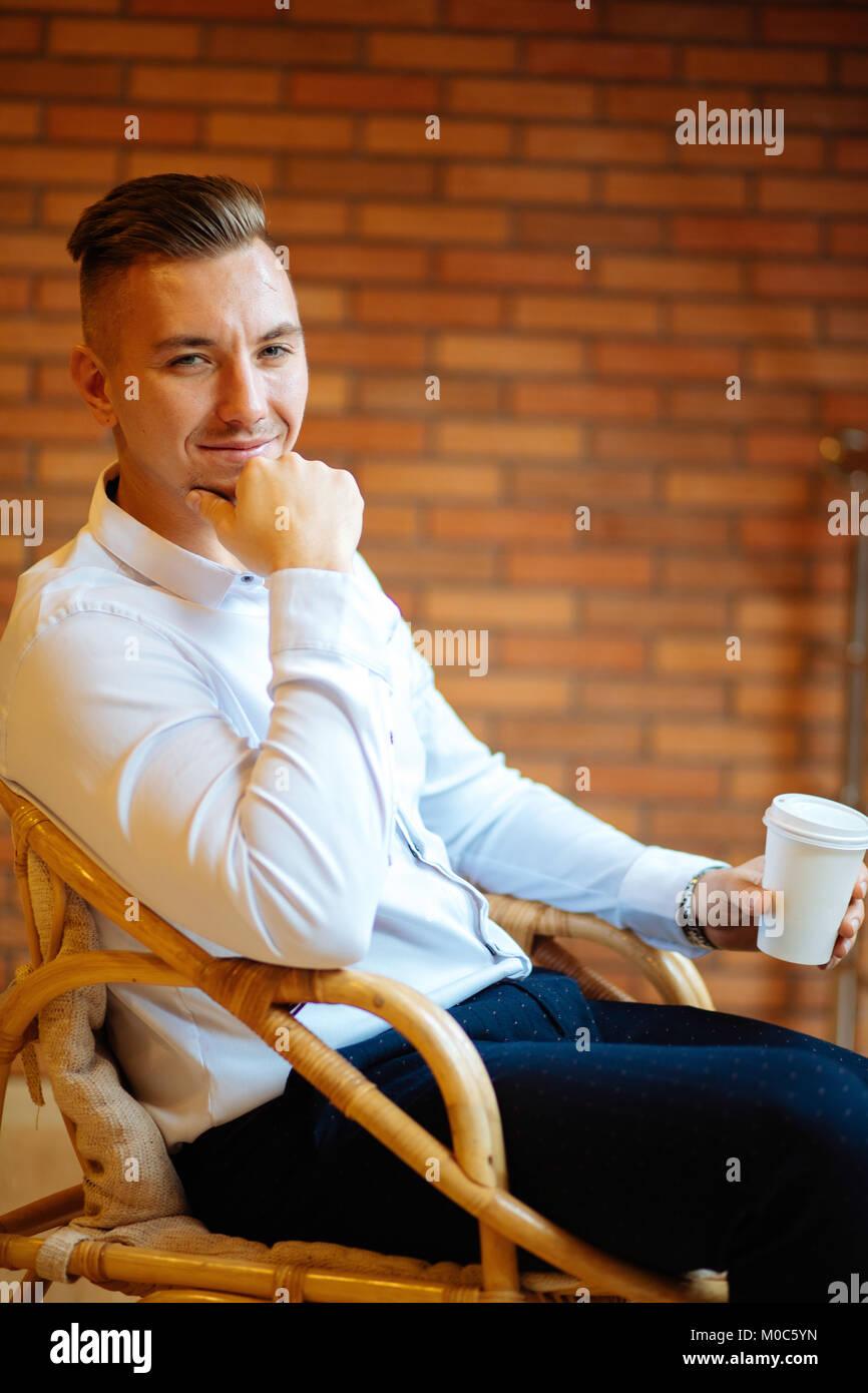 Gut aussehender Geschäftsmann trinken Kaffee im Haus und suchen Kamera Stockbild