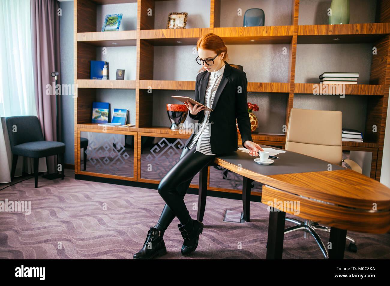Attraktive Geschäftsfrau, die auf einem digitalen Tablet-PC im Büro. Stockbild