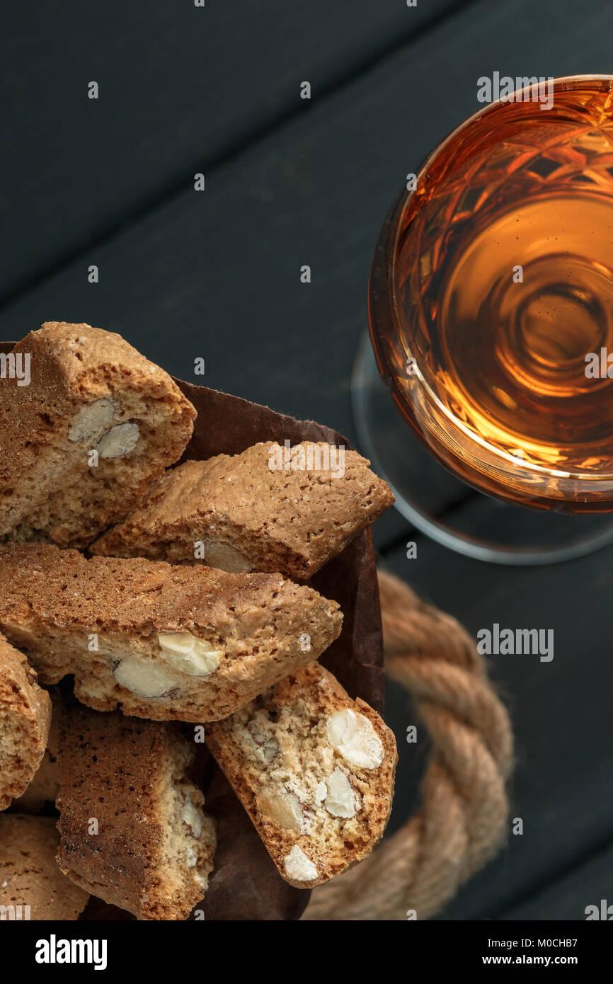 Italienische cantuccini Gebäck und ein Glas süßen Vin Santo Wein über Holz- Hintergrund Stockfoto