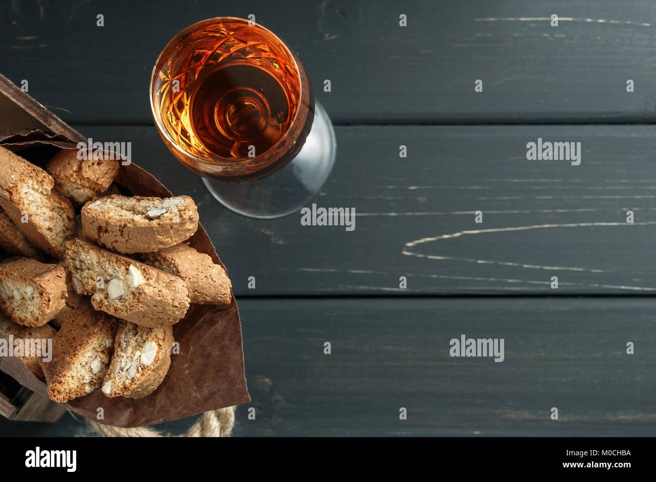 Italienische cantuccini Gebäck und ein Glas süßen Vin Santo Wein über Holz- Hintergrund Stockbild