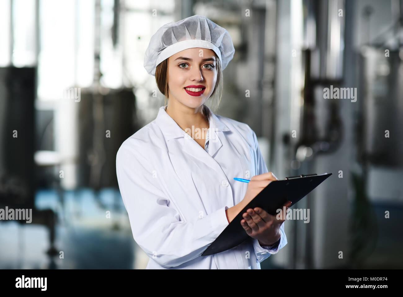 Süße Mädchen in weißen Arbeitskleidung macht sich Notizen auf einem Stift auf einem Tablet Stockbild