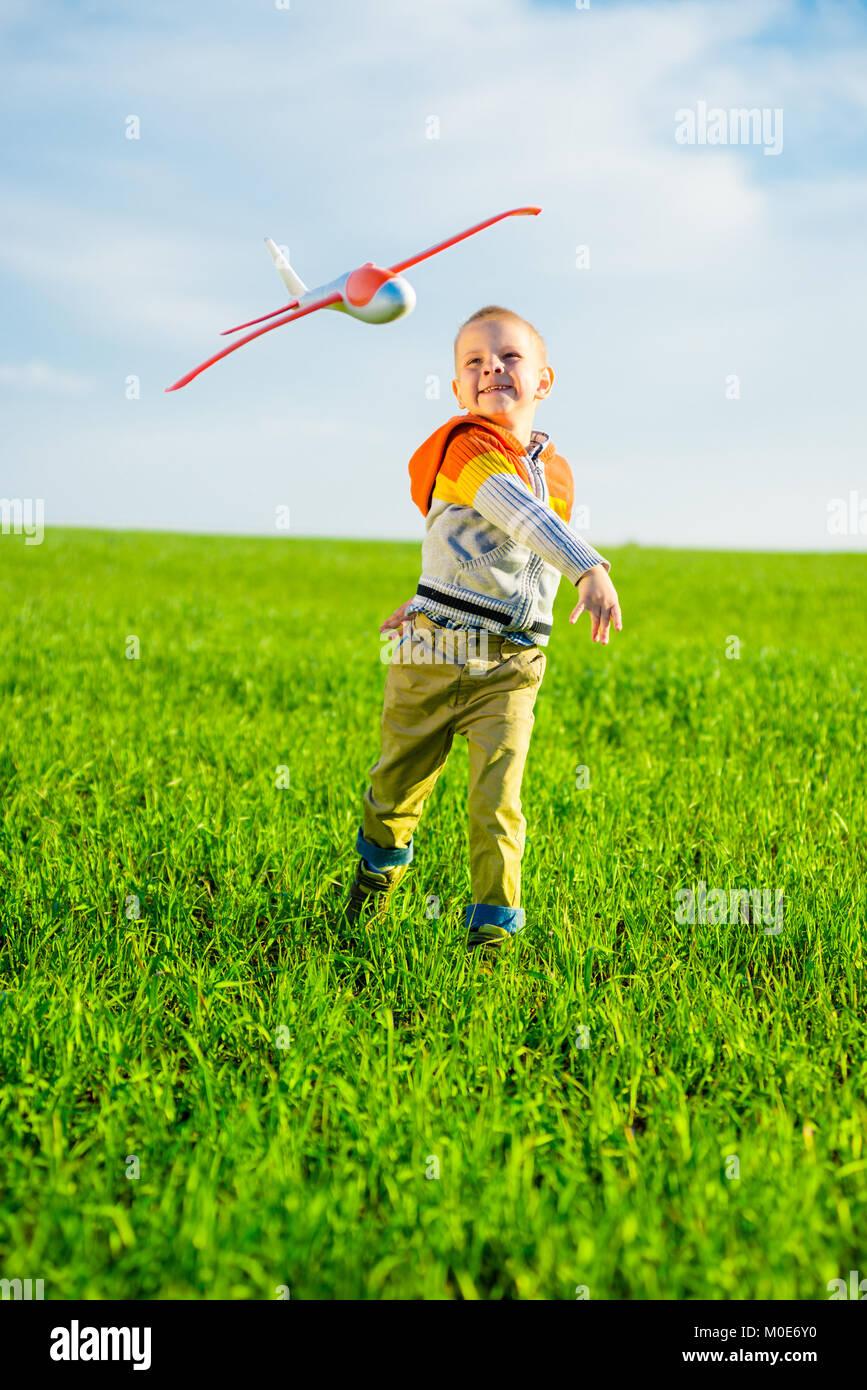 Fröhlicher Junge spielt mit Spielzeugflugzeug gegen blauen Himmel und grüne Feld Hintergrund. Stockbild