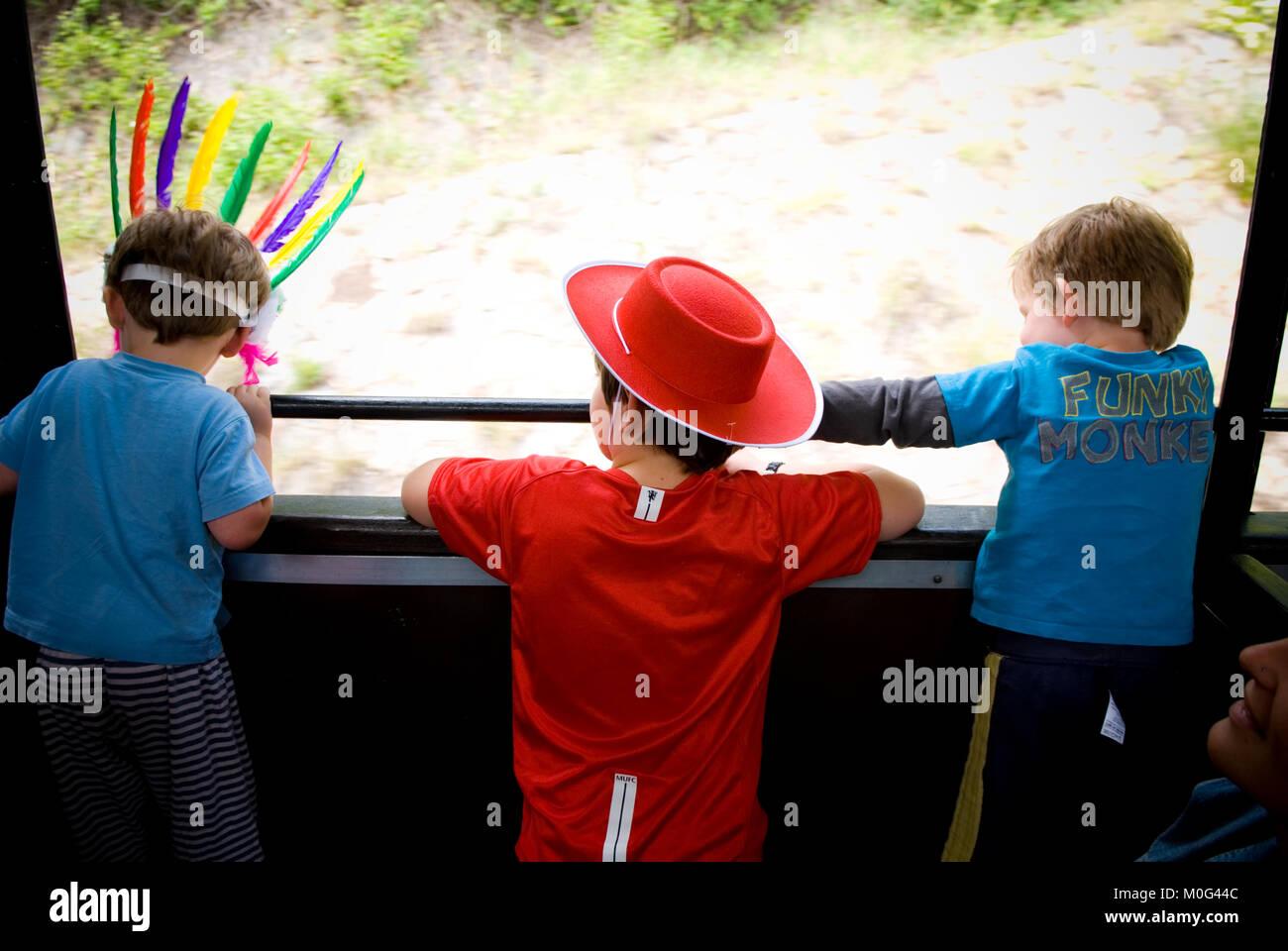Hintere Aufnahme von drei Jungen, zwischen zwei Jahren getarnt als Indianer und Cowboy, Blick aus Fenster des fahrenden Stockbild