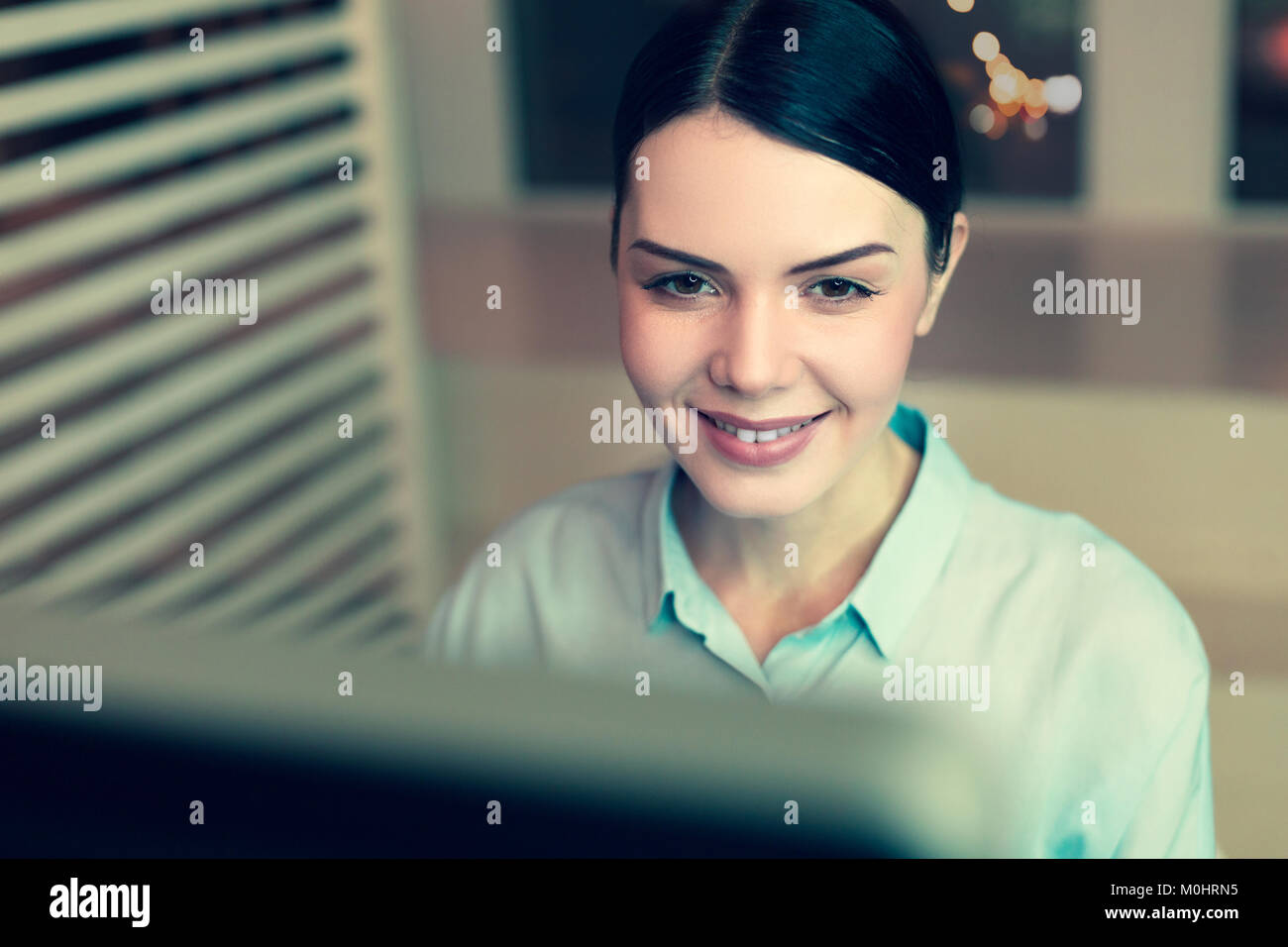 Fröhliche dunkelhaarige Frau Arbeiten am Computer Stockbild