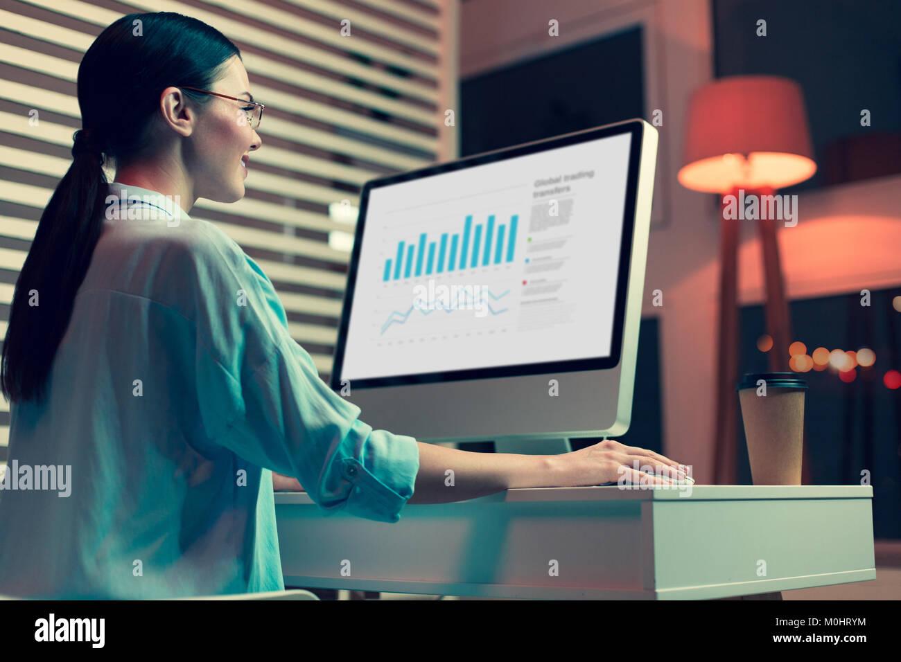 Lächelnd weibliche Analytiker Erstellen von Graphen und Diagrammen Stockbild