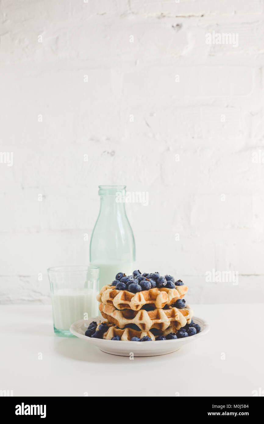 Köstliches Frühstück mit Waffeln mit Blaubeeren und Glas Milch Stockbild