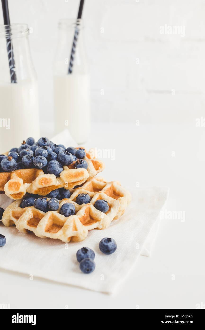 Köstliches Frühstück mit frisch gebackenen Waffeln mit Heidelbeeren und Milch Stockbild