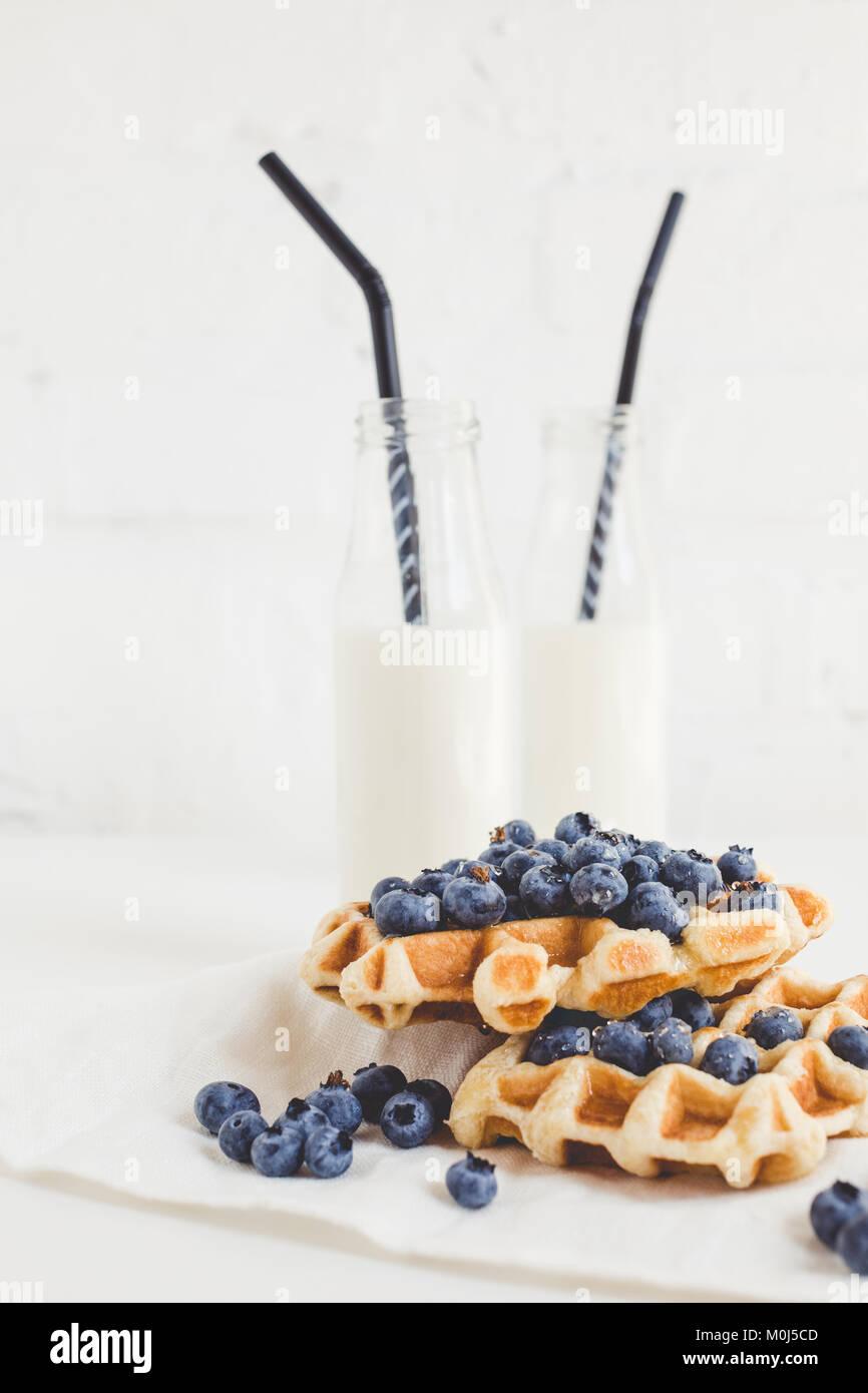 Köstliches Frühstück mit frischen Waffeln mit Heidelbeeren und Milch Stockbild
