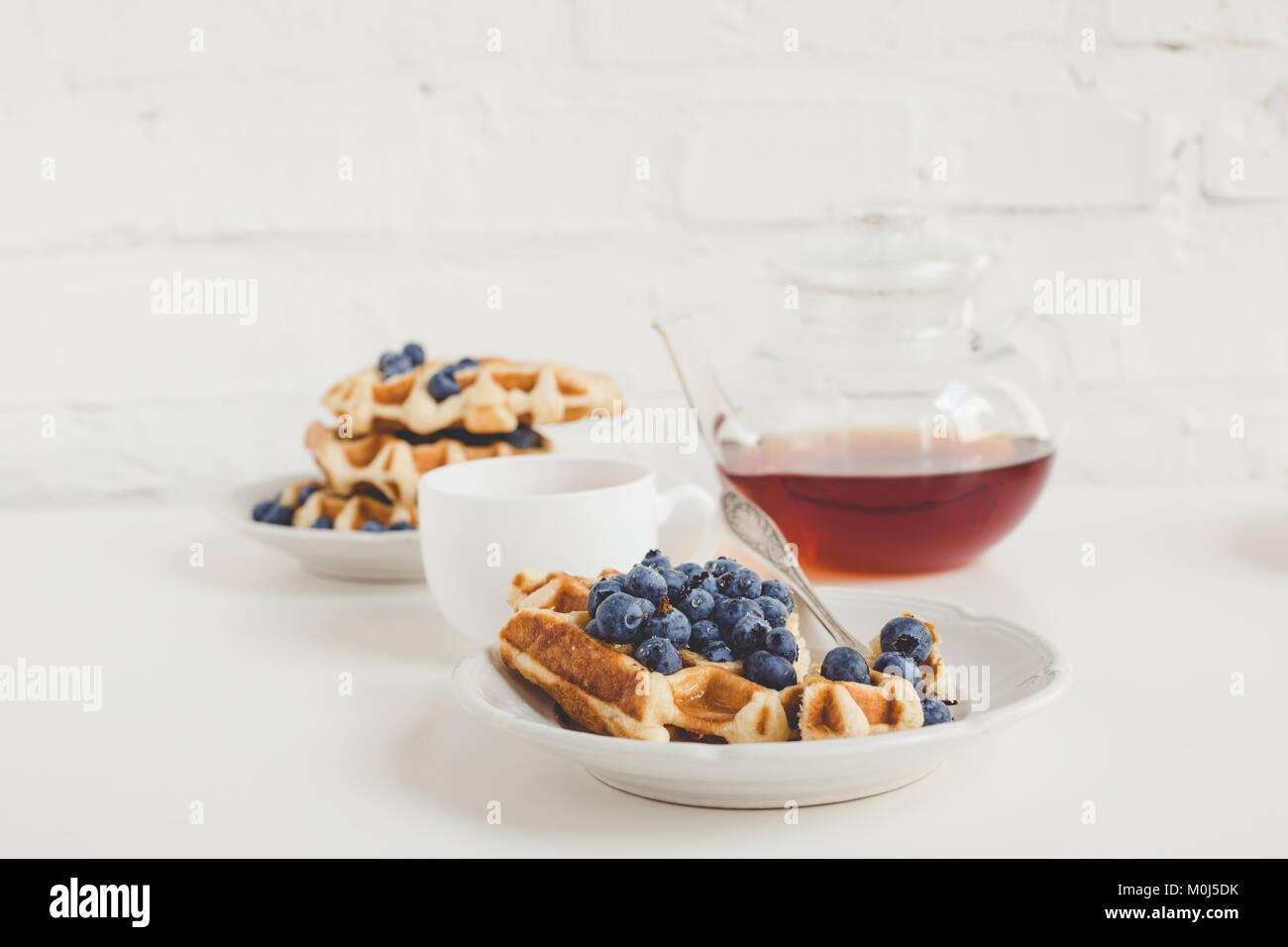 Köstliches Frühstück mit frisch gebackenen Waffeln mit Heidelbeeren und Kaffee Stockbild