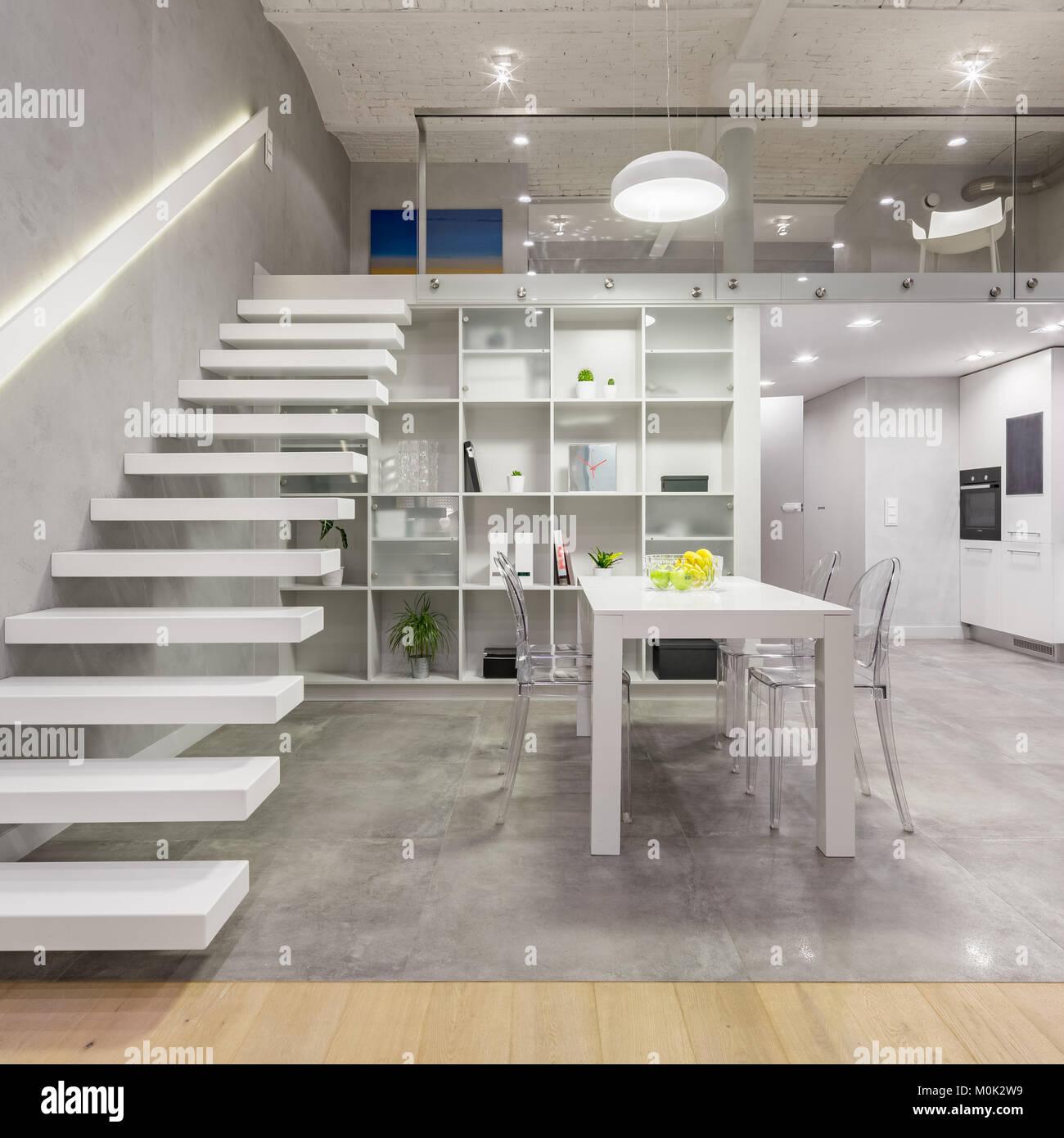 Loft Apartment mit weißen mezzanine Treppe, Tisch, Stühlen ...
