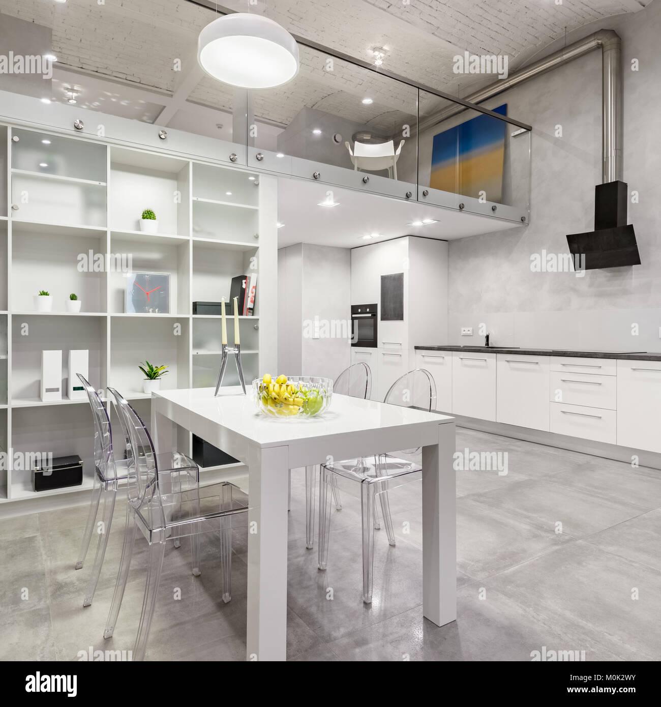 Loft Interieur mit weißer Tisch, transparenten Stühle und ...