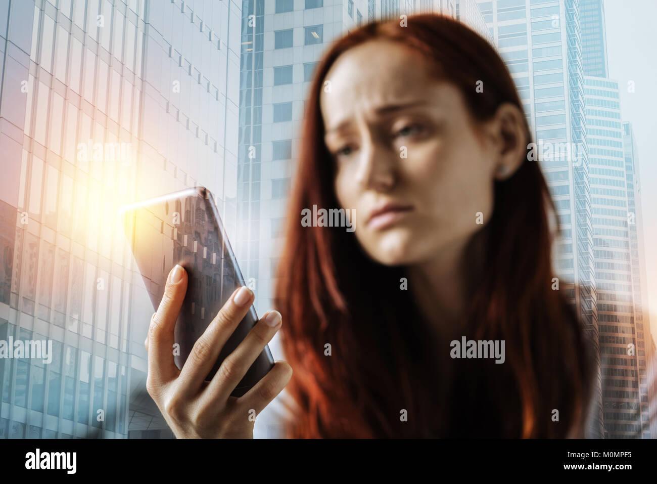 Unglücklich rothaarige Frau mit Handy und es zu verwenden. Stockbild