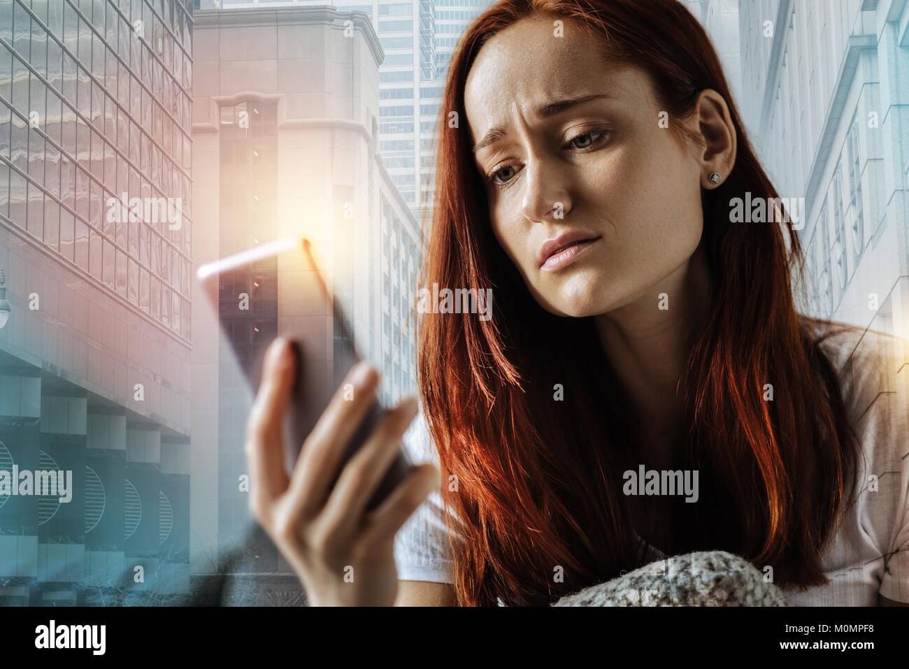 Traurige junge Frau sitzt und mit dem Handy. Stockbild