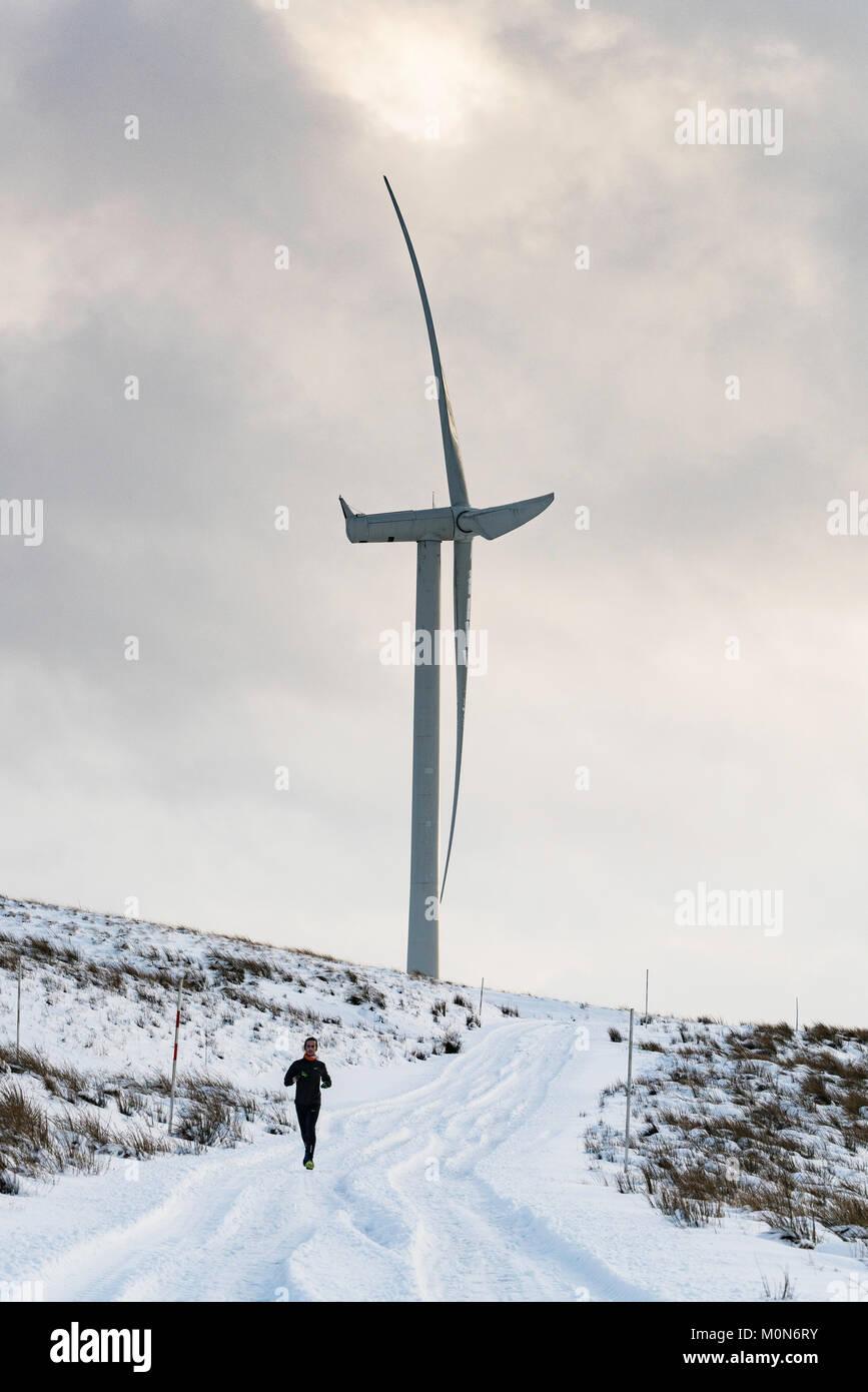 Mann laufen im Schnee neben Windenergieanlage im Windpark Whitelee im East Renfrewshire von Scottish Power betrieben, Stockbild
