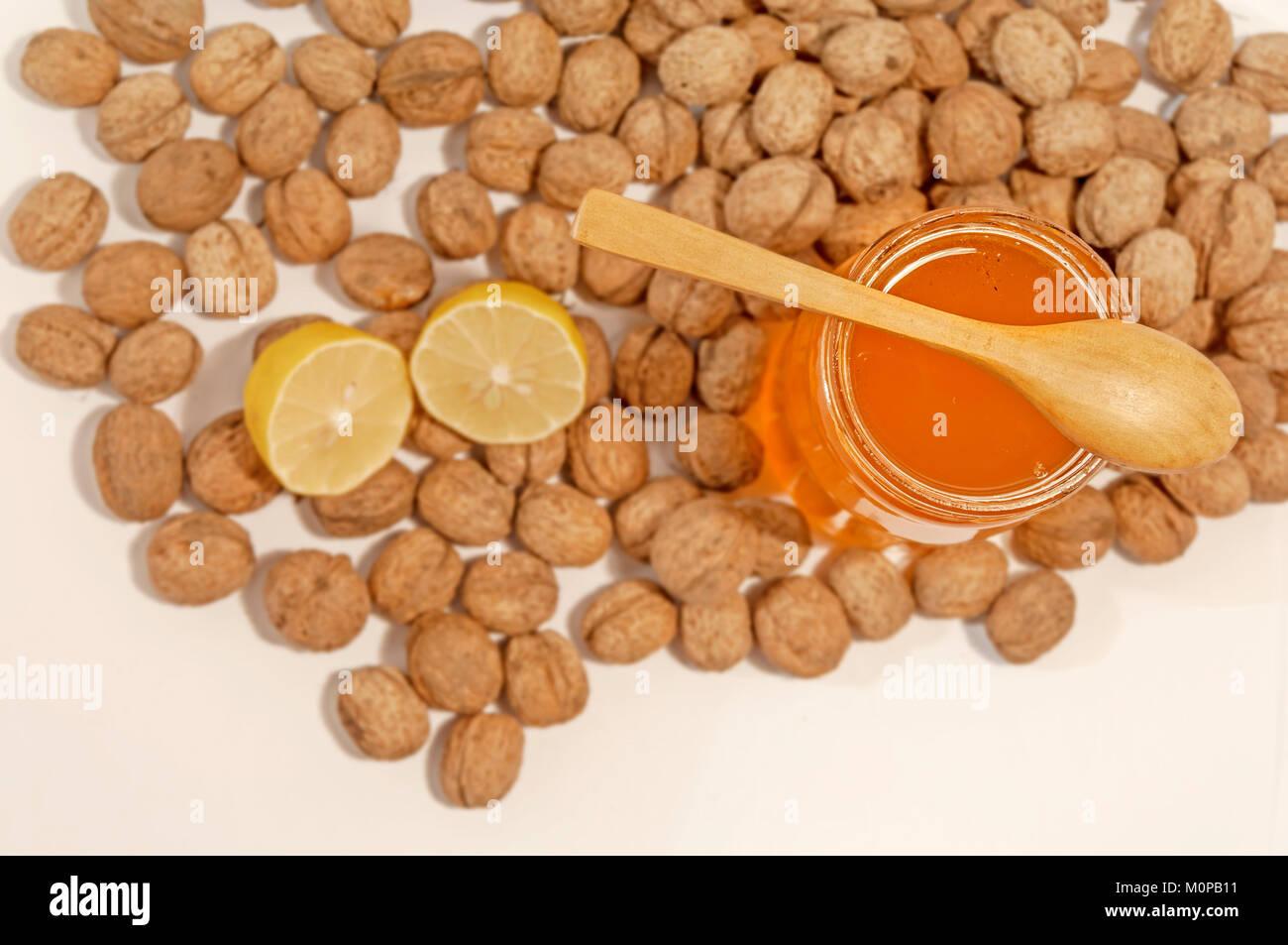 Krug Honig und Löffel mit Zitrone und Walnüsse Stockbild