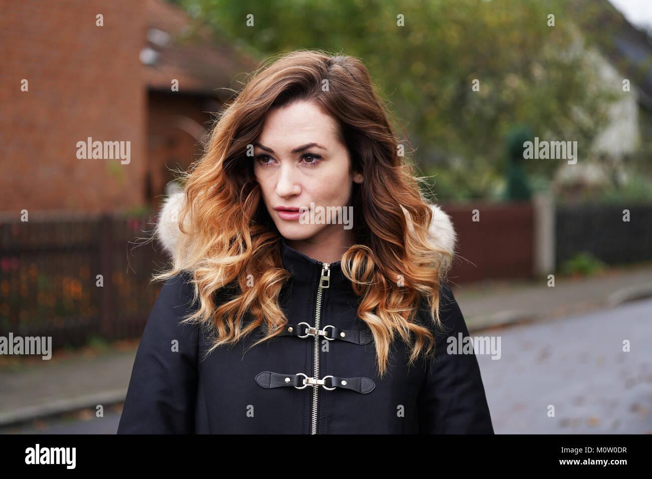 Junge Frau tragen winter Fell ist in Gedanken auf Vorstadtstraße verloren Stockbild