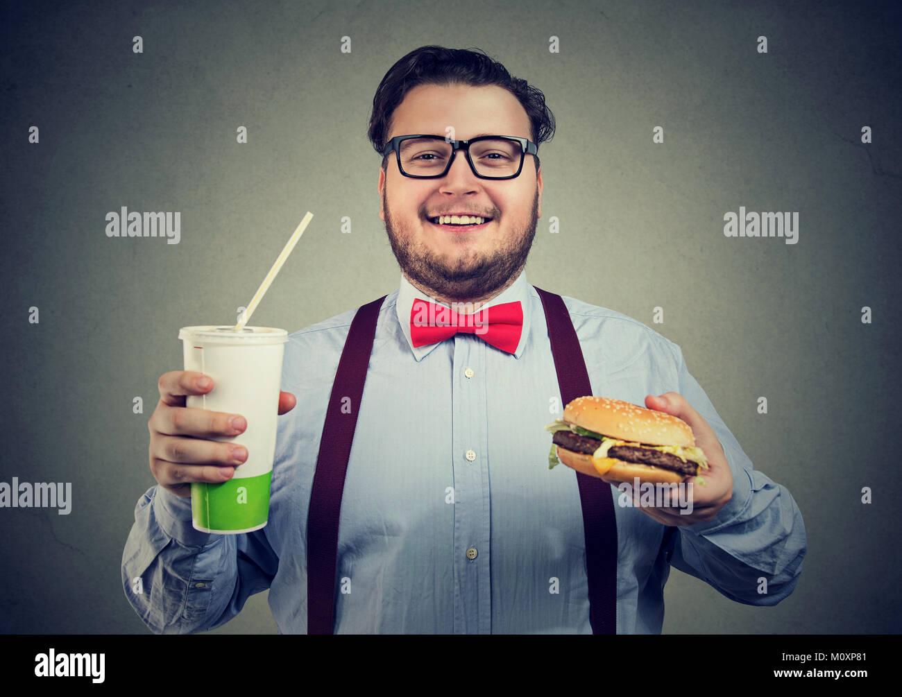 Junge Glücklich, aufgeregt, während mit Burger und Soda an der Kamera schaut. Stockbild