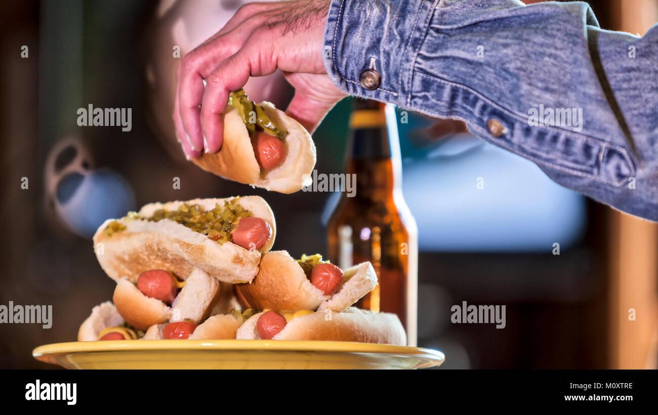 Ein Bachelor man Fernsehen und essen Hot Dogs. Stockfoto