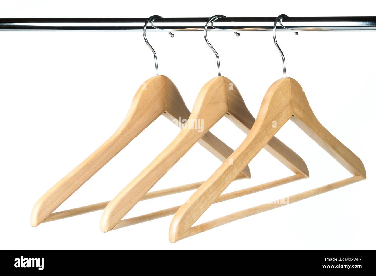 Drei Holz- Mantel-/Kleiderbügel auf einer Kleiderstange mit einem ...