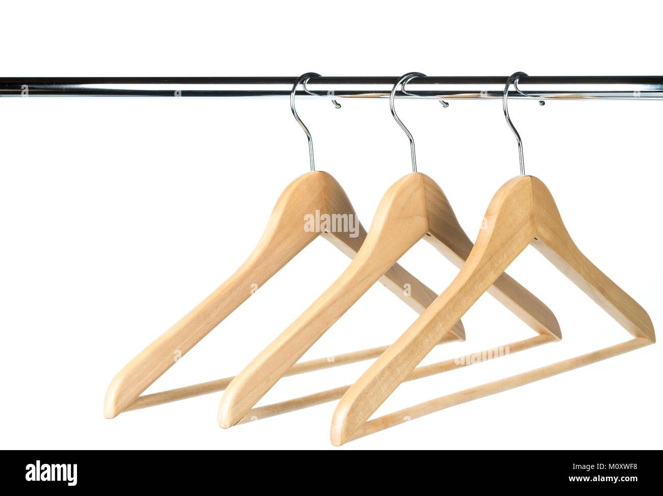 Drei leere Holz- Mantel-/Kleiderbügel auf einer Kleiderstange mit ...