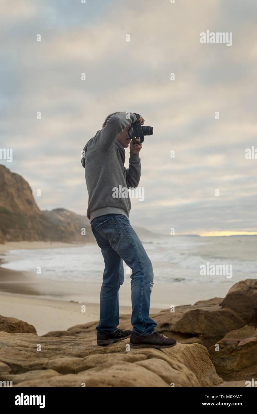 Mann, auf den Felsen an der Küste Fotografieren mit DSLR-Kamera. Stockfoto