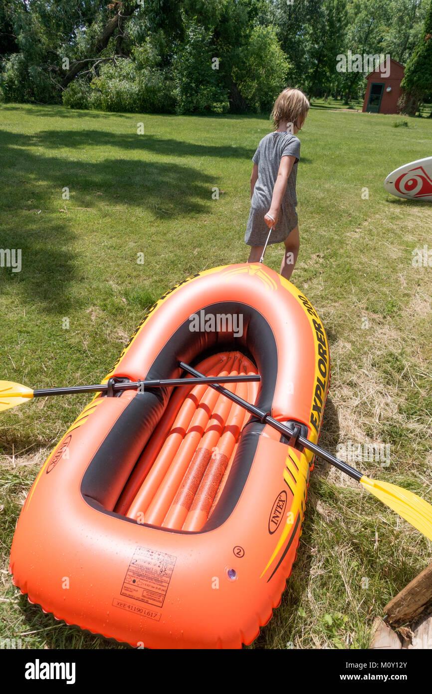 Mädchen im Alter von 10 hat ihr Teil, indem Sie ihr Schlauchboot zu hohen Boden nach einem Tag voller Spaß Stockbild