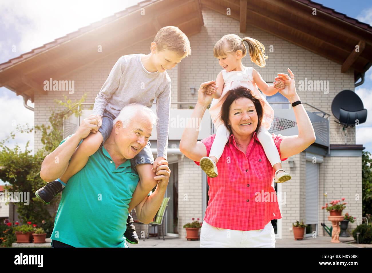 Lächelnd Enkelkinder sitzen auf der Großeltern Schulter außerhalb Ihres Hauses genießen. Stockbild