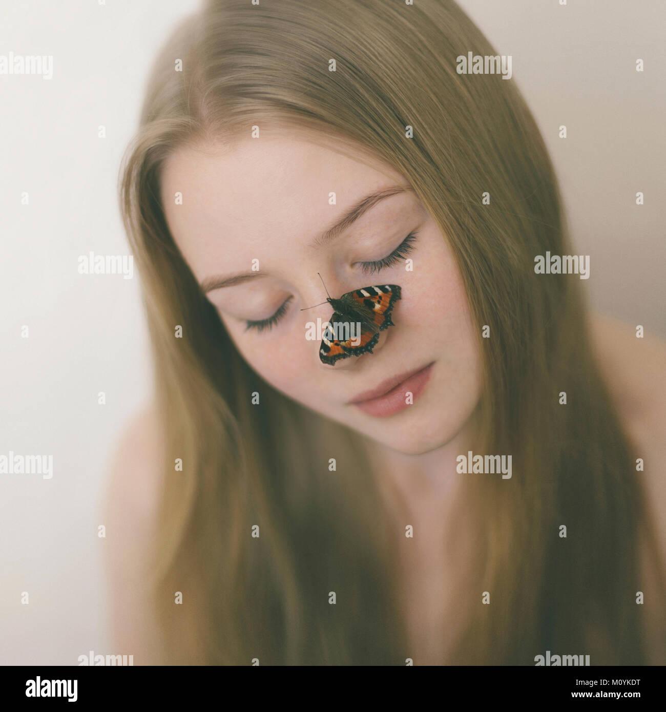 Schmetterling auf der Nase der kaukasischen Jugendmädchen Stockfoto