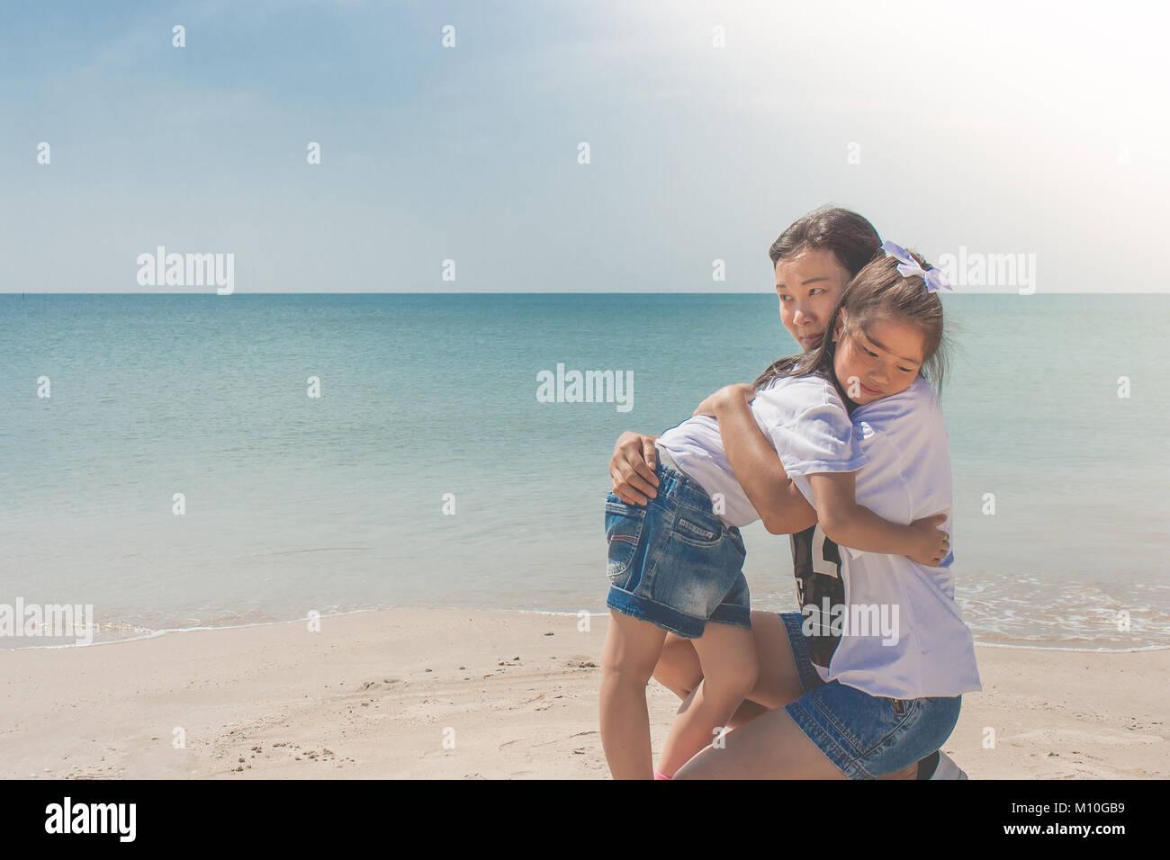 Adorable und Familie Konzept: Frau und Kind umarmen und Gefühl Glück auf Sand Strand mit Blick auf das Meer im Hintergrund. Stockfoto
