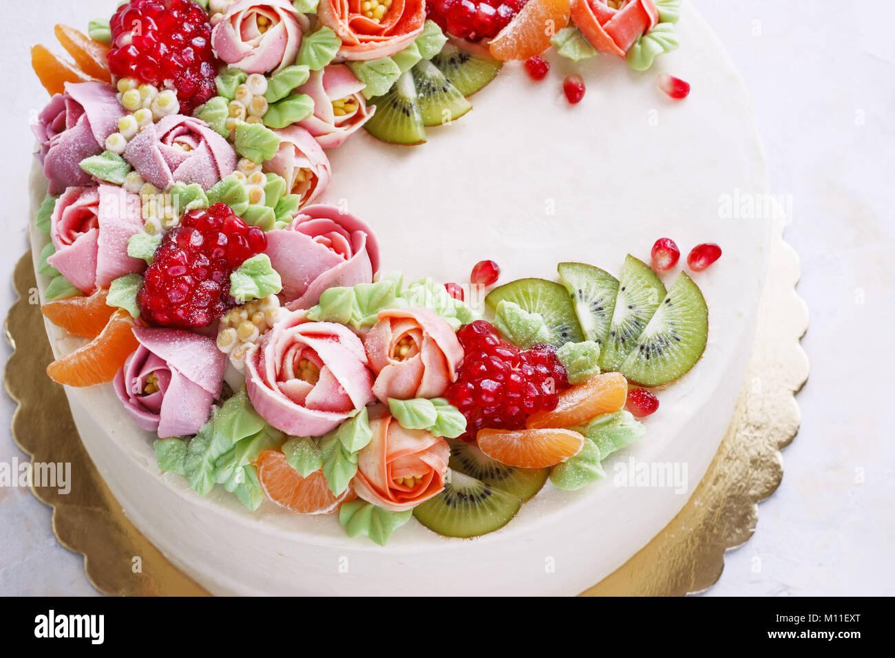 Festliche Kuchen mit cremefarbenen Blüten und Früchte auf einem hellen Hintergrund Stockbild