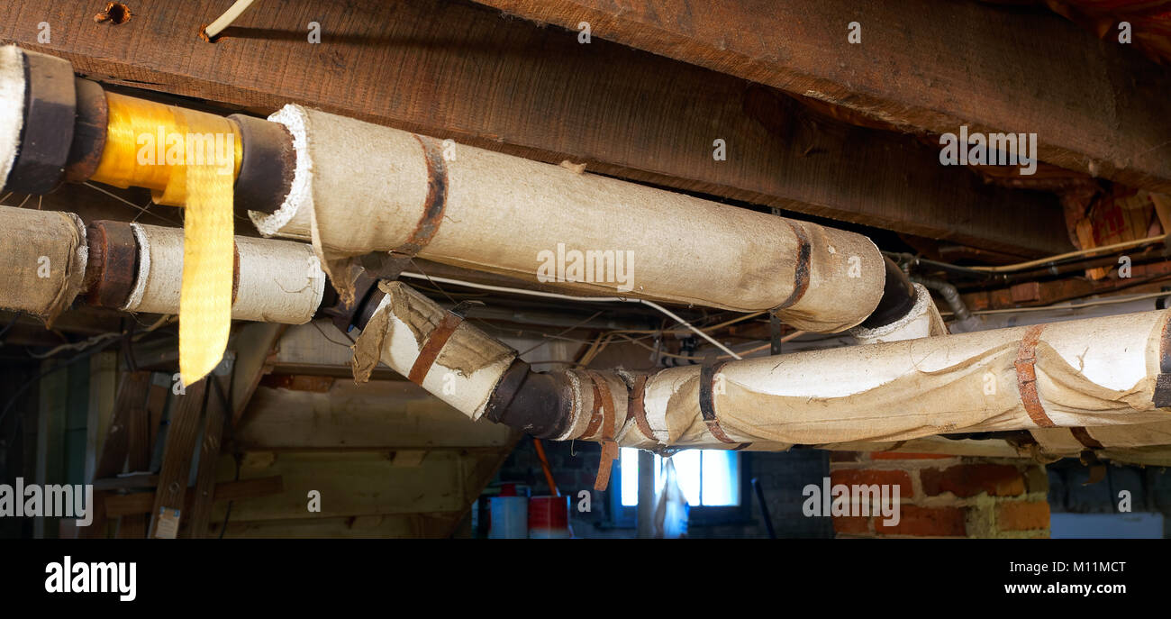 Sehr Keller Wasserleitungen mit Asbest Isolierung umwickelt Stockfoto YN88