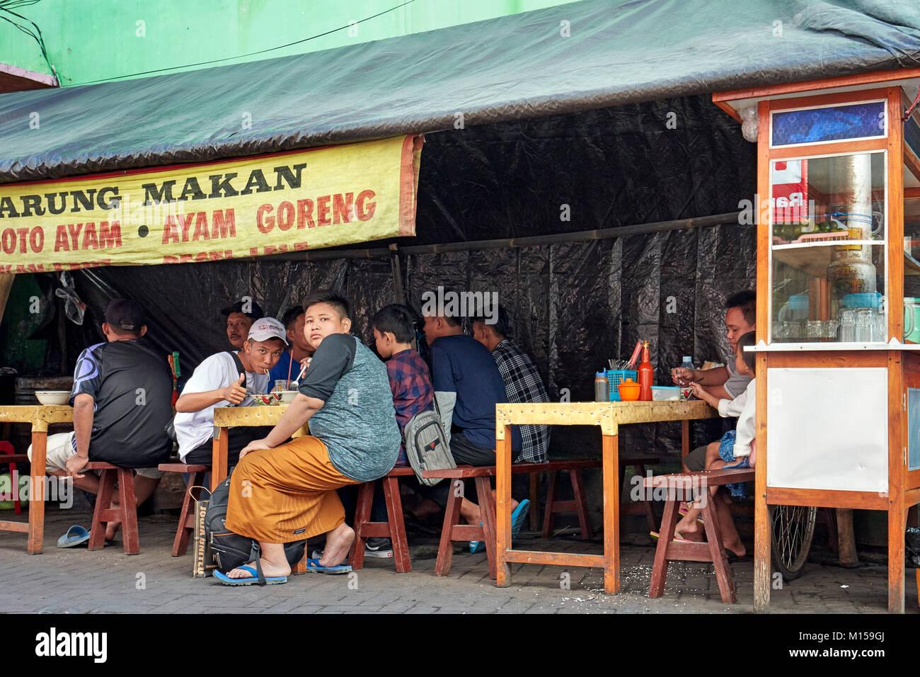 Menschen essen in einem kleinen Restaurant auf der Straße Ketandan Wetan Straße. Yogyakarta, Java, Indonesien. Stockbild