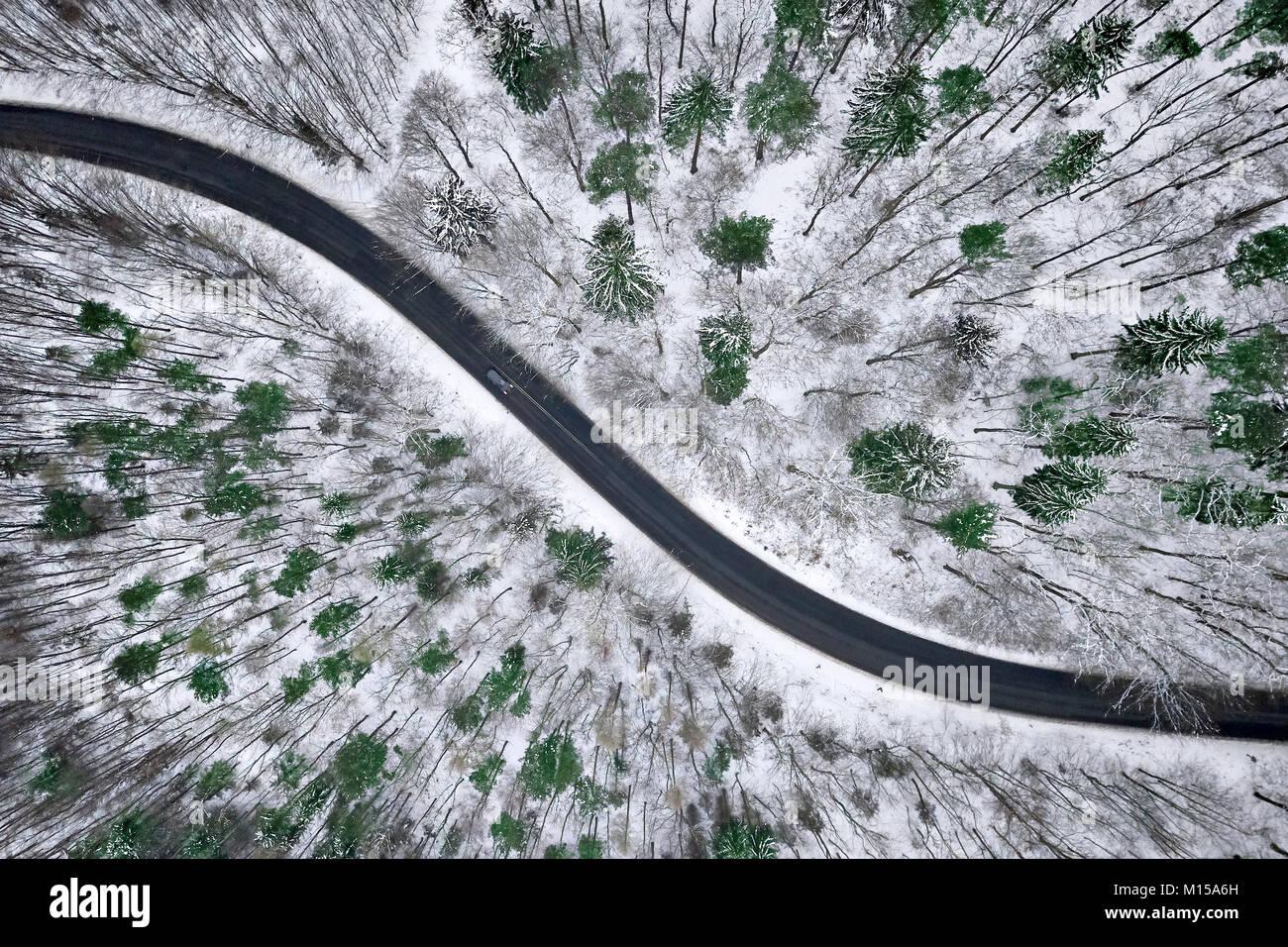Luftaufnahme von winter Straße im verschneiten Wald. Drohne erfasst Schuß von oben. Stockbild