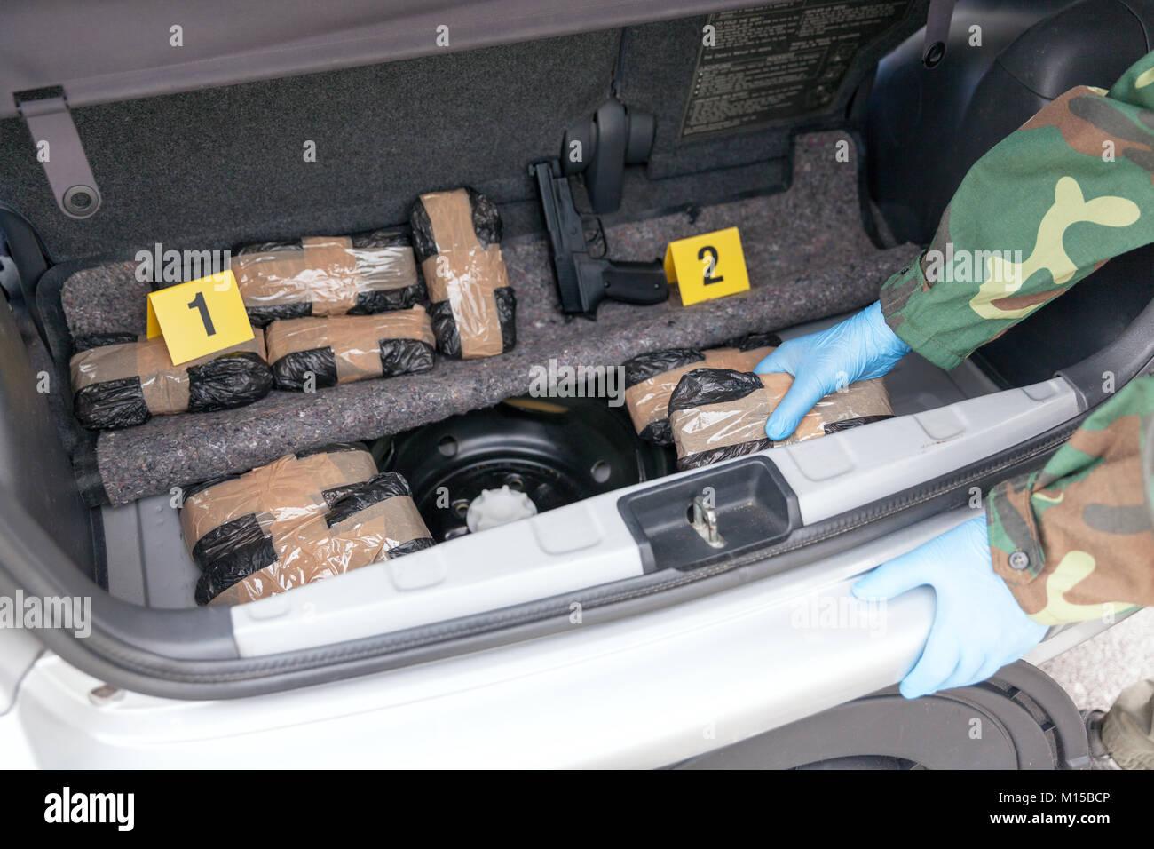 Polizeioffizier holding Droge Paket im Kofferraum eines Autos ...