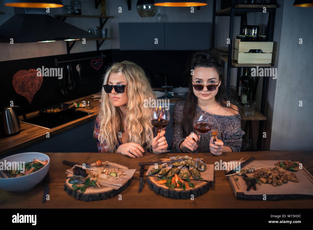 Zwei junge Frauen hält Gläser Wein in der modernen Küche zu Hause ...