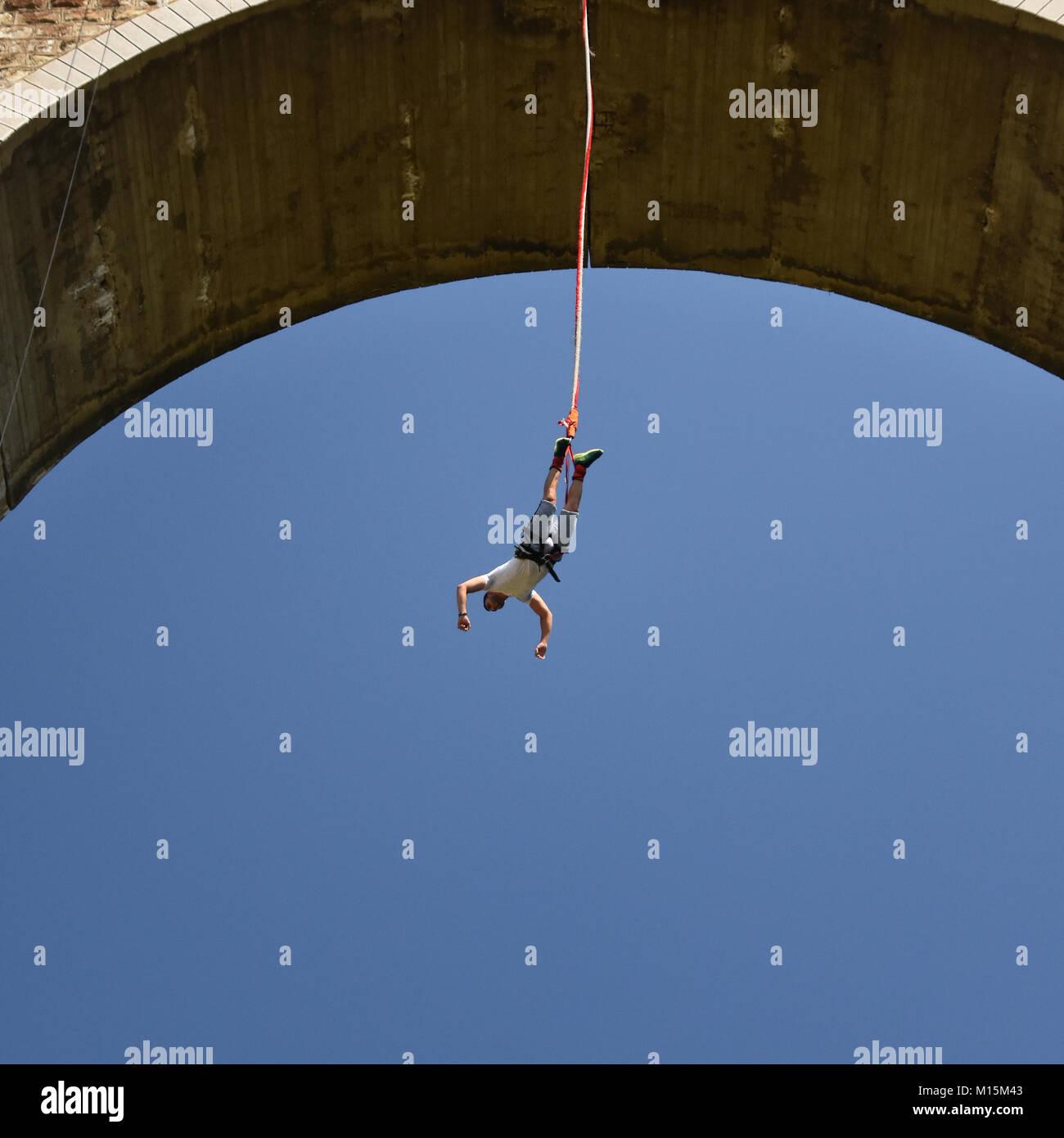 junger mann bungee jumper auf einer schnur aufhängen stockfoto, bild