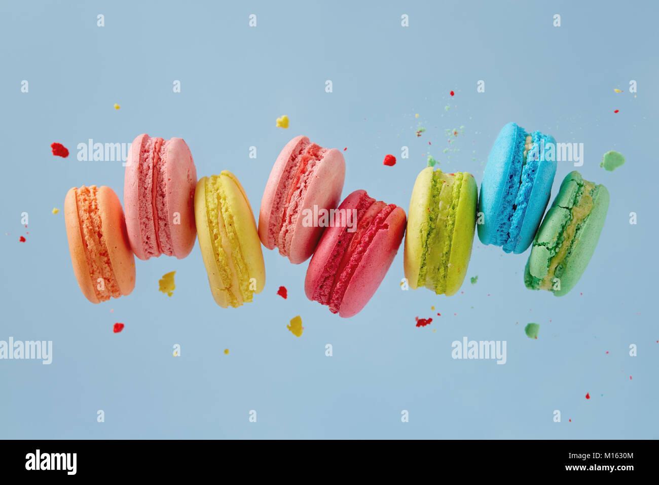 Verschiedene Arten von Makronen in Bewegung fallen auf blauem Hintergrund. Süße und bunte französische Stockbild