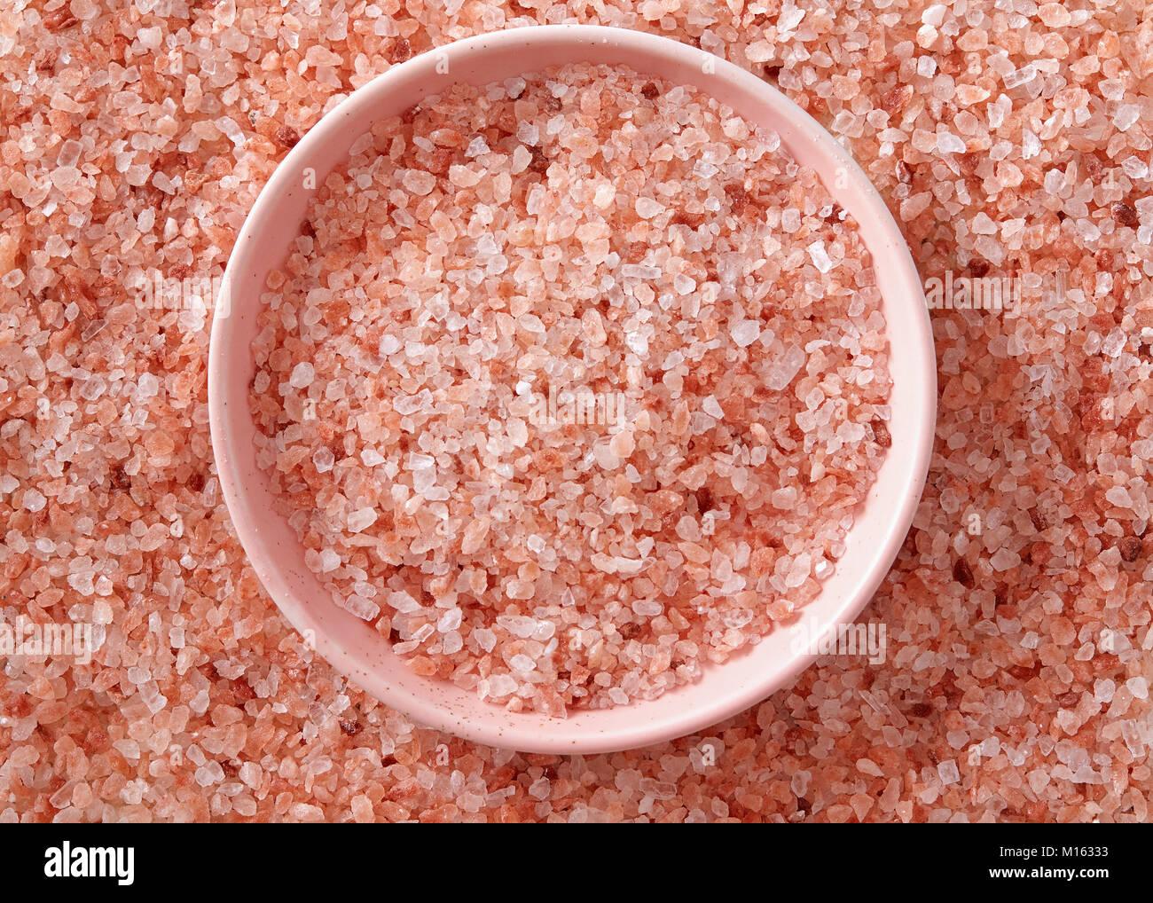Rosa Himalaya Salz in der kleinen rosa Schüssel. Eine kleine rosa Schüssel voll der Salzkristalle. Stockbild