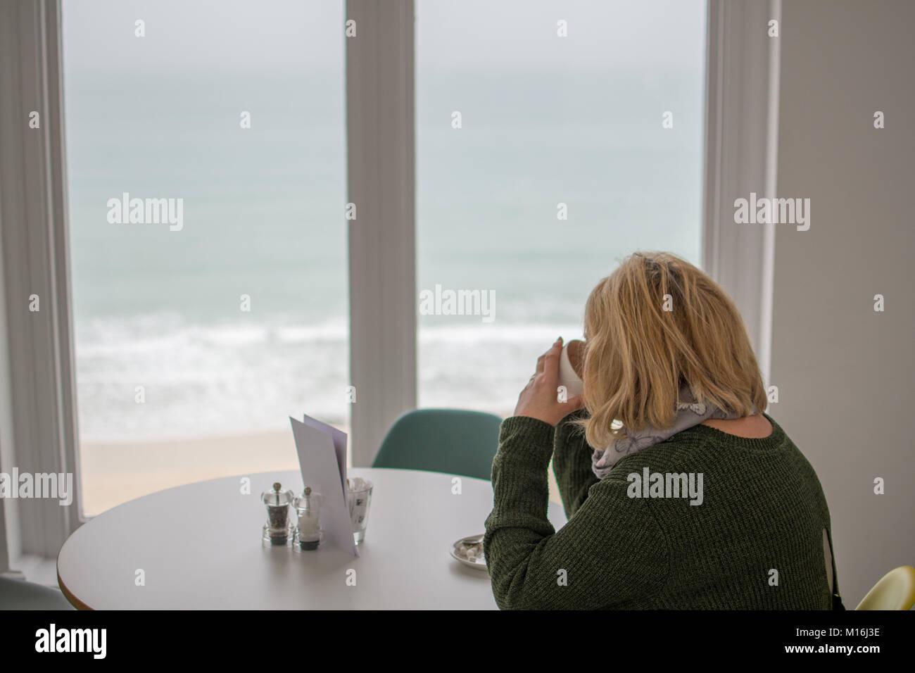 Frau trinkt Kaffee vor einem Fenster mit Blick auf den Strand und das Meer in St. Ives in Cornwall. Stockbild