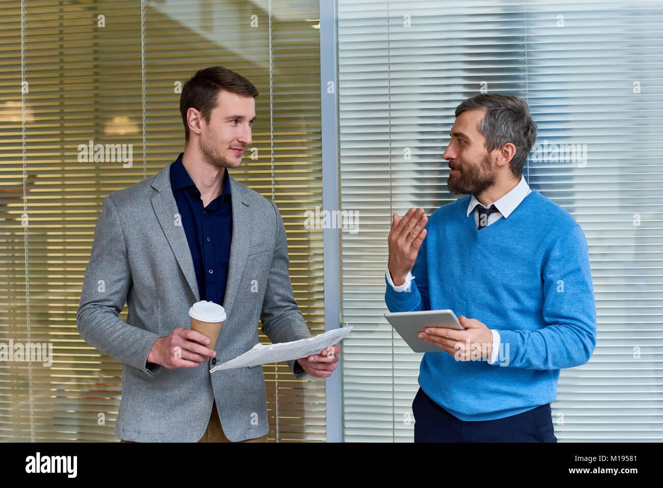 Geschäft Leute diskutieren News im Büro Stockbild