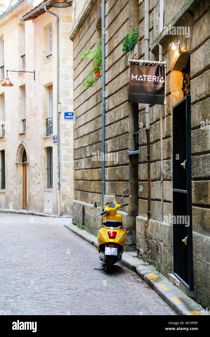 Gelbe Motorroller geparkt in der Rue du Puits Descujols, Bordeaux, Gironde, Nouvelle-Aquitaine, Frankreich. Stockbild