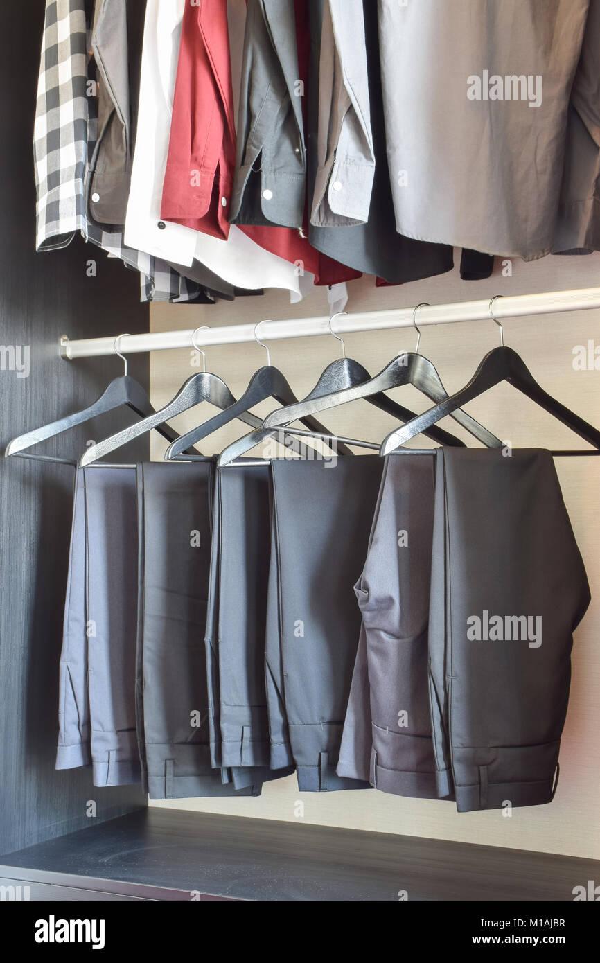 Reihe Von Hosen Und Shirts In Den Kleiderschrank Aus Holz Aufhängen